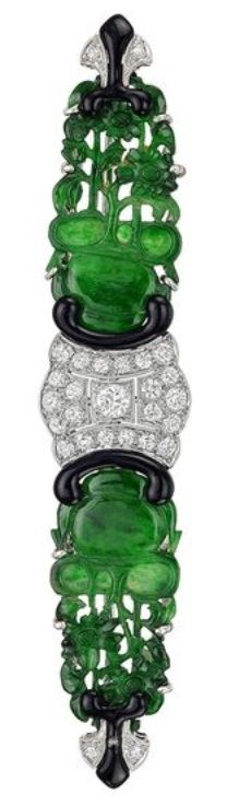 An Art Deco Carved Jade and Diamond Brooch, by J.E. Caldwell, 1920s. Featuring a pair of fine pierced jadeite panels framed by 27 round diamonds, with black enamel accents, mounted in platinum. Signed 'JEC' for J.E. Caldwell. 3.45 x 0.7 in. #Caldwell #ArtDeco #brooch