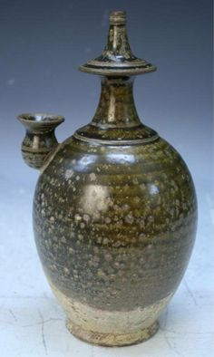 "Covered jar with tea dust glaze used for blessing in Buddhist temple (glaze has 38%-42% iron), ceramic, China, Ming Dynasty (1368-1644); unmarked. Dimensions: 10""H x 5-1/2"" diameter"