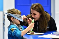 The Duchess of Cambridge helps blindfolded Fynley Gooch, aged seven, ice a cake as she promotes disability awareness when she met with children at the newly established 23rd Poplar Beaver Scout Colony in east London