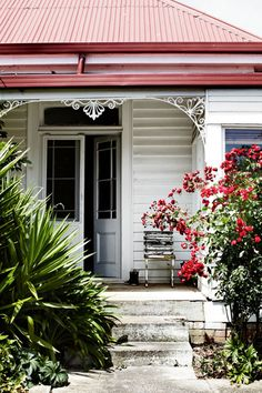the style files - front porch in South Africa - flowering bush, french doors, rustic chair, wellie boots by the door - this has it all.
