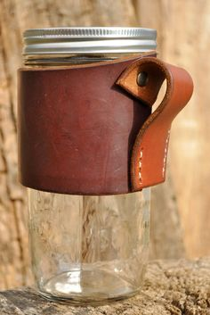 Custom made leather koozie. Hand dyed. Hand tooled. Hand stitched. Made from vegetable tanned leather. Designed to fit a 24 ounce mason jar(included). Fits great in your cup holder and travels well in a bag for days on the go. Leather protects your hands from hot coffee/tea and insulates icy cold beverages. Brighten up your day with your favorite drink! Three lid options available: Regular lid, Lid with straw hole, or $7 for a Cuppow coffee lid.