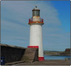 Lighthouse on Whitehaven Harbour's (England) West Pier was built in 1841. The white tower with red trim is built into the breakwater which has two levels, joined by cases of 17 steps. From this location you can see at least 3 other lighthouses, including the other towers within the harbour and the Trinity House Lighthouse at St. Bees Head.