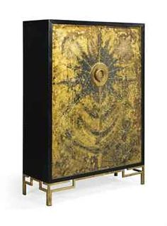 MAISON JANSEN, ATTRIBUTED  CABINET, 20th CENTURY  Ebonised wood, with patinated and incised brass doors, on brass feet and including brass shelves,