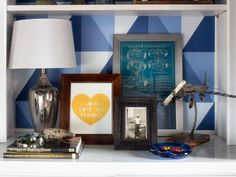 This bookcase was styled with framed art and vintage family photos as well as a mix of reflective materials in the mercury glass table lamp, vintage model propeller plane and framed mechanical blueprint.