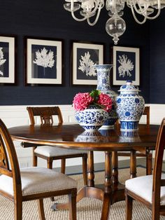 Crisp white wainscoting, navy blue walls provide perfect backdrop for traditional dining table with lovely blue & white china arrangement. Note the small, med, large placement of the china!