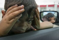 A migrant boy peers through a car window at a petrol station turned migrant camp near Polycastro, Greece, Wednesday, May 25, 2016. Refugees and other migrants were boarding buses heading to organized camps Monday on the second day of an operation to evacuate the sprawling Idomeni refugee camp on the Greek-Macedonian border.