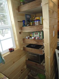 The Brevard Tiny House pantry.note the pull out drawer with induction cook tops.and the drawer below it wit the tiny house microwave. This is a unique way to save on limited counter space