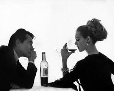 Model wearing Bersoie organza dress, sharing a bottle of Chateau Lafite-Rothschild wine with Italian actor Walter Chiari, photo by Bert Stern, April 1962