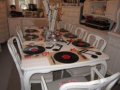 Love this table decor using records and sheet music for place setting whimsy; great for a musical theme party/dinner party.