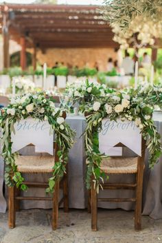 Gorgeous floral garland topped sweetheart chair: http://www.stylemepretty.com/little-black-book-blog/2016/02/01/rustic-elegant-crete-destination-wedding-2/ | Photography: Anna Roussos - http://www.annaroussos.com/