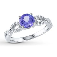 A round tanzanite is accompanied by icy white diamond accents in this captivating engagement ring for her. Crafted in 10K white gold, the ring has a total diamond weight of 1/15 carat. Diamond Total Carat Weight may range from .065 - .08 carats. Gently clean by rinsing in warm water and drying with a soft cloth.