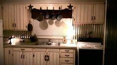 barn wood backsplash | Tin backsplash off white barn wood cabinets with vintage hardware