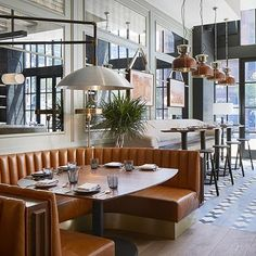 The Proxi Restaurant Chicago by Meyer Davis. Terracotta tan leather circle booth banquette with mirror panels and suspended wall mounted pendants