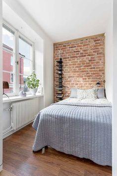 aménagement petite chambre avec mur d'accent de brique, étagère verticale et literie grise