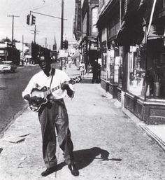 John Lee Hooker plays on Detroits Hastings Street, late 1940s. Check out his flecked wool pleated pants and sharp shiny shoes!