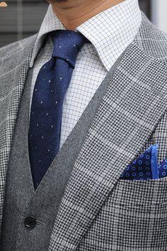 ●スリーピースのスーツスタイル スーツはチェック柄の2つボタンスーツ。スーツのグレーに合わせて、グレーフランネルのオッドベストを合わせました。ネクタイの柄はできれば無地調やプレーンなドット柄がおすすめです。今回はネイビー地に小さい白のドットが入ったウールタイをチョイスしてみました。ポケットチーフはネクタイのネービーに合わせて、シルク100%の小紋柄プリントをチョイスしています。DSC_0004-500