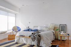 La silla azul dicta el tono que se repite en el acolchado reversible (Arredo) y en la alfombra rayada (Graciela Churba). Sobre la cama, almohadones lisos y estampados (Petite Margot).  Foto:Living /Daniel Karp