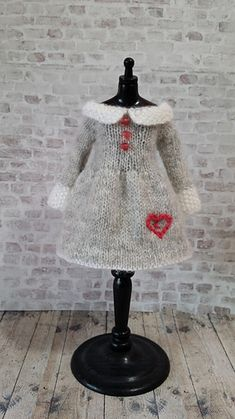 Sweet little fine knit dress for your Blythe doll. Uses laceweight yarn and is knit from the collar down in one piece with sleeve and back seam.