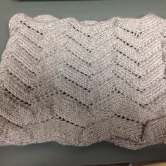 """Perfect for summer walks along the beach,the Seventh Wave Cowl is designed to be light and breezy,worn loose or wrapped a couple of times around the neck for added warmth against the wind. A simple lace chevron pattern, suitable for beginning lace knitters, mimics the shape and shadows of gentle waves. The bottom """"wave"""" is doubled in size to represent the seventh wave often purported to be larger than all the rest. This also helps to visually anchor the bottom of the cowl.The cowl is…"""