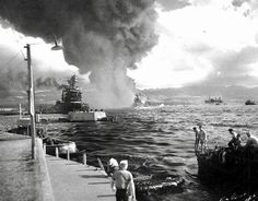 """Pearl Harbor Attack 7 December 1941 Caption: """"View looking down """"Battleship Row"""" from Ford Island Naval Air Station, shortly after the Japanese torpedo plane attack. USS California (BB-44) is at left, listing to port after receiving two torpedo hits. In the center are USS Maryland (BB-46) with the capsized USS Oklahoma (BB-37) alongside. USS Neosho (AO-23) is at right, backing clear of the area. Most smoke is from USS Arizona (BB-39)."""" (Official U.S. Navy Photograph, now in the collections of"""