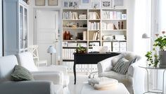 A white living room with bookshelves and armchairs