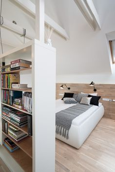 OOOOX | PLZEN - bedroom with wooden headboard and white leather bed. freestanding bookcase