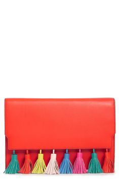 A line of swingy tassels lends a festive upgrade to this sleek leather clutch in a pop of color.