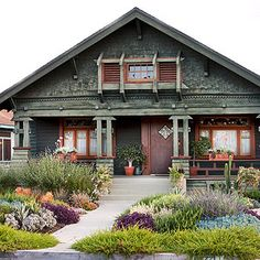 love the look of the landscaping of this house!  no grass.  also, love those structures around the windows!  and the color scheme.