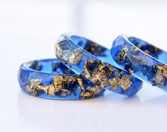 This blue resin ring contains metallic copper flakes suspended in hand pigmented blue resin. You can wear only one or you can stack two or three rings on a finger. You can also contact me for a custom color request, if you have something else in mind! This listing is for ONE blue resin ring with copper flakes. Handmade by me from scratch, each one of my pieces is hand pigmented, and poured into a silicone mold. After I remove it from the mold I hand sand it for you to have a smooth and…