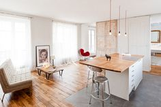 Open plan living room with kitchen island - the neutral grey floor tile appears on the countertop as cutting board