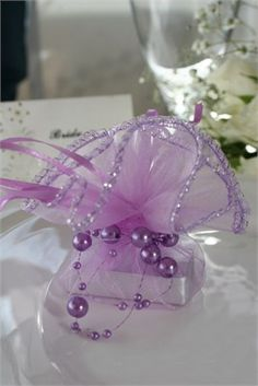 Square sized chocolate (approx 4 cm x 4 cm) wrapped in silver-foiled paper beautifully presented in a lilac purple organza (pull-ribbon tie) bag with sparkly silver edging. A beautiful lilac pearl (on wire thread) bow is tied around for the finishing touch.Available in a variety of colours - please contact us for requests.