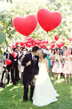Bride and groom with balloons and all of their wedding guests