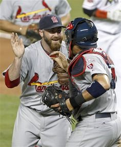 St. Louis Cardinals pitcher Jason Motte, left, celebrates with catcher Yadier Molina after the Cardinals defeated the Miami Marlins 4-1i n the Opening-Day baseball game, Wednesday, April 4, 2012, in Miami.