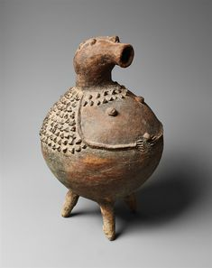 Lot 94 - A GA'ANDA TERRACOTA VESSEL In the form of a figure with arms in relief on the spherical body, the