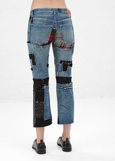 Wide jean in washed cotton denim. Zip fly with button closure. Classic five pocket styling. Black sequined and embroidered attachment detail in a wool blend throughout. Red and black plaid attachment at rear. Dry clean only.