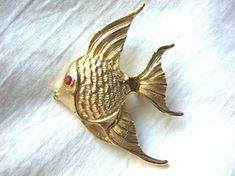 Picturehis sweet vintage gold-tone angelfish pin brooch is probably from the 1960s or 1970s. It is highly detailed with textured scales and textured full flowing tail and fins. It has a bright red, faceted rhinestone for its eye. It is approximately 1 7/8 inches wide and 1 inch tall.