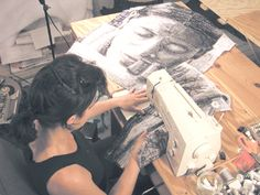"""Fiber Artist Terese Agnew working on """"Portrait of a Textile Worker"""", a quilted image made of clothing tags."""