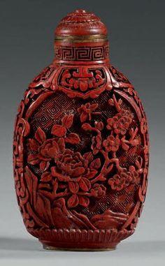 Flacon tabatière en résine imitant le laque rouge sculpté à décor de pivoines. Chine, début du XXe siècle. Hauteur: 6,5 cm Bouchon de même m...