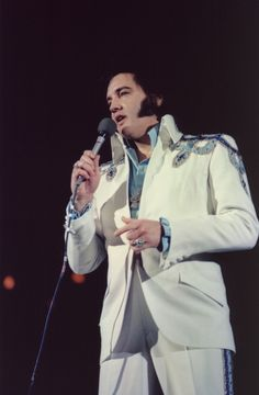 BENEFIT SHOW in NATIVE STATE! ELVIS wearing the two-piece BENEFIT suit on May 30 1975 in Jackson, MS at State Fair Coliseum. THE KING raised $108,860 For Victims Of Tornado. A white sleeveless jumpsuit, white jacket with blue and silver trim on the shoulders and silver lined kickpleats done in embroidery on the legs. Worn with a light blue satin puffy shirt and the famous Maltese Cross necklace. A belt was made, but ELVIS never wore it with this suit. Photo: George Hill.