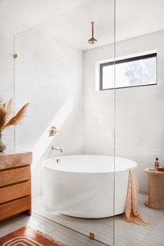 "Garance Doré enlisted the help of designer Sarah Sherman Samuel to assist with revamping her home into a minimalist-modern oasis. Signature Hardware's 55"" Dempsey Round Acrylic Freestanding Tub complements the terracotta tones of the master bathroom and serves as the perfect choice for having a stand-alone tub in the walk in shower."