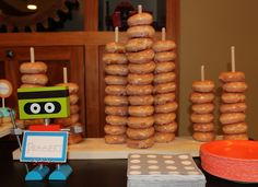 Dessert Buffet - My son made this mini donut stand the night before the party.  Cut dowels, drilled holes and stuck the dowels into a board.  He even stopped to get some #KrispieKreme mini #donuts to make sure the spacing was right. - Robot Birthday Party #robot #robotparty #diy #dessert