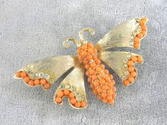 Beautiful textured gold tone butterfly pin by Ledo. There are faux coral beads on the edges of its wings along with brilliant rhinestones