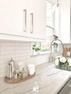 Quartzite stone window sill with wood trim window framing between window and adjacent upper cabinetry. Carla Aston, Designer | Colleen Scott, Photographer #kitchensink #kitchenwindow