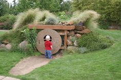 "From CroqZine: ""We went to the Oregon Garden a few days ago, and I was happy to see this ""hobbit hole"" in the children's garden! I would love to have one of these in my yard!! It was made with a big drainage tube, and had round plywood doors on each end of the tube. The earth had been mounded over the tube and then covered with grass and plants. They built a nice T-shaped door frame over the hobbit door, and there you go! """