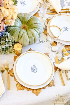 Elegant Heirloom Thanksgiving Table Scape with blue, purple and white hydrangeas, blue ginger jars, and green heirloom pumpkins. Monogram plates and gold flatware, stemware, chargers, and votives.   - Randi Garrett Design