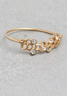 LARA MELCHIOR & OTHER STORIES Crafted from sterling silver with gold plating, this thin and delicate ring features a finely cut honeycomb design with rhinestones inlaid in five of the cutouts.
