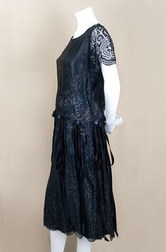 New York silk lace dress, c.1924 The dress is constructed with two separate layers attached at the neckline, shoulders, and drop waist. The slip-style under layer is of black silk chiffon with a skirt lining of black China silk, attached black lace sleeves, and a satin ribbon cummerbund. The lace over dress is decorated with velvet ribbon rosettes and streamers that hang from the base of the cummerbund. Each layer closes separately with hooks and snaps. Side 3