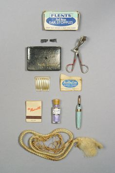 Marilyn's beauty items, including an eyelash curler, a set of Martha Lorraine eyelashes (in original box), a box of Flents ear stopples, a lipstick brush, a bottle of violet eye shadow, a haircomb, and a book of matches from the St. Regis Hotel. Provenience: Julien's Auctions.