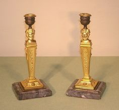"""A pair of early 19th Century bronze and ormolu French candlesticks, having garland moulded sconces above classical heads with moustaches and grape and grapevine decoration, supported on classical """"terms"""" fitted with musical instruments to the sides, ending on moulded grey square marble bases. Circa: 1810 Ref: 5608"""