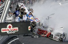 Officials look at the engine and tire of driver Kyle Larson's car after he was involved in a multi-car crash at the conclusion of the NASCAR Nationwide Series.
